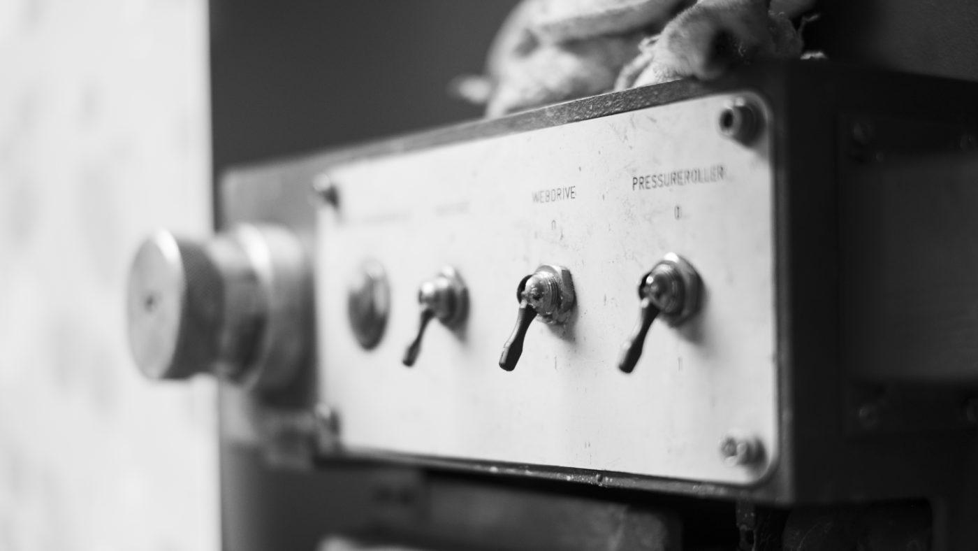 Detaljbild på  knappar på maskin i tapetfabriken.